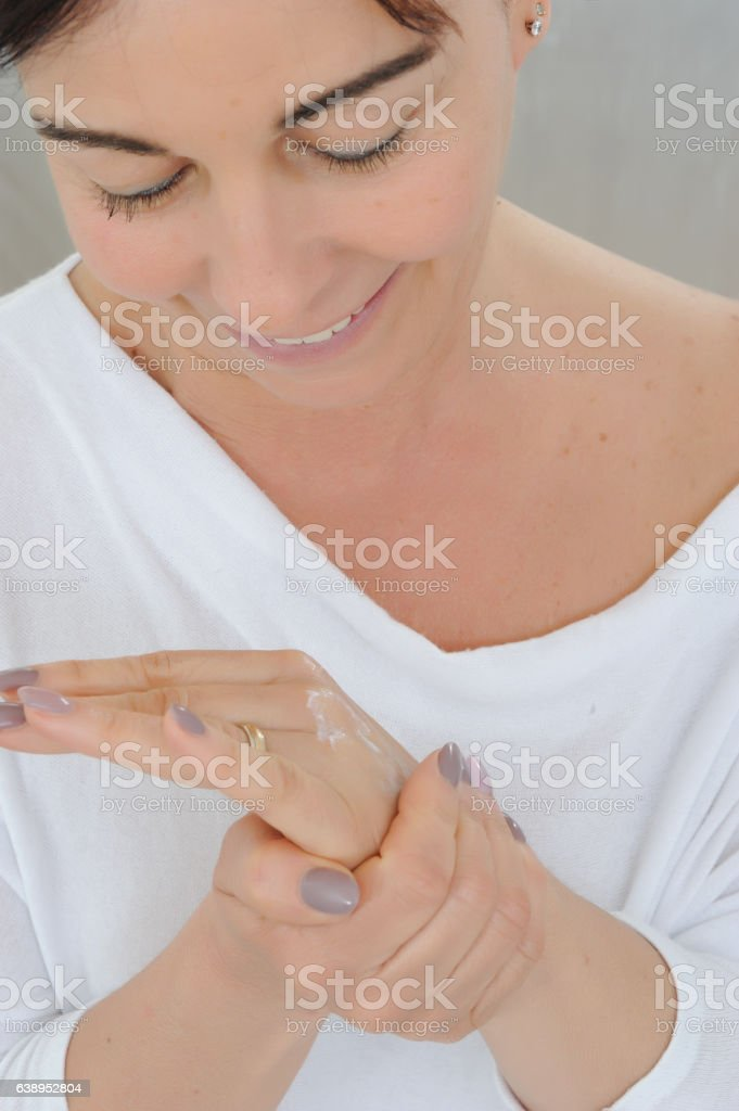 middle aged woman applying cream on hands stock photo