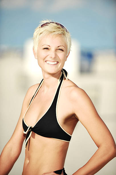 Middle Aged Woman at Beach Middle Aged Blond Woman at beach wearing bikini middle aged women in bikinis stock pictures, royalty-free photos & images