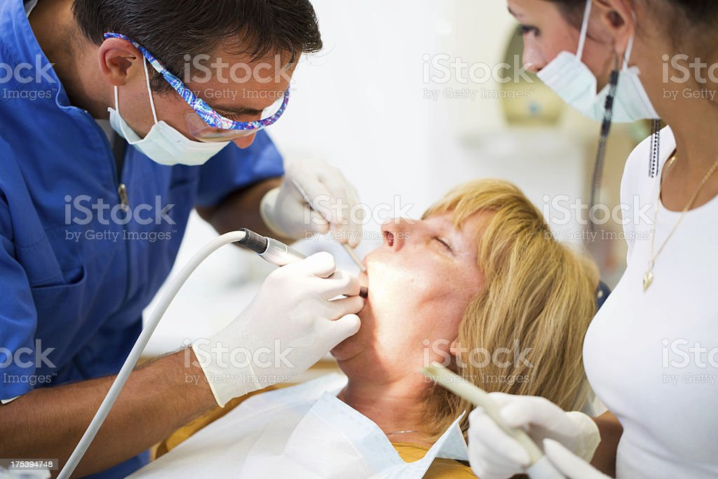 Middle aged woman at the dentist...doctor and nurse working royalty-free stock photo