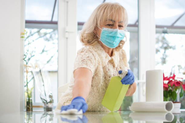 Middle aged woman cleaning the table with spray disinfectant and paper tissue at home. Corona virus preventive measures. stock photo