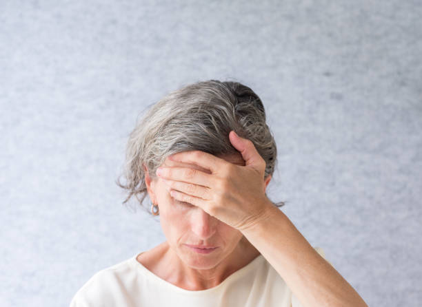 Middle aged woman covering eyes with hand stock photo