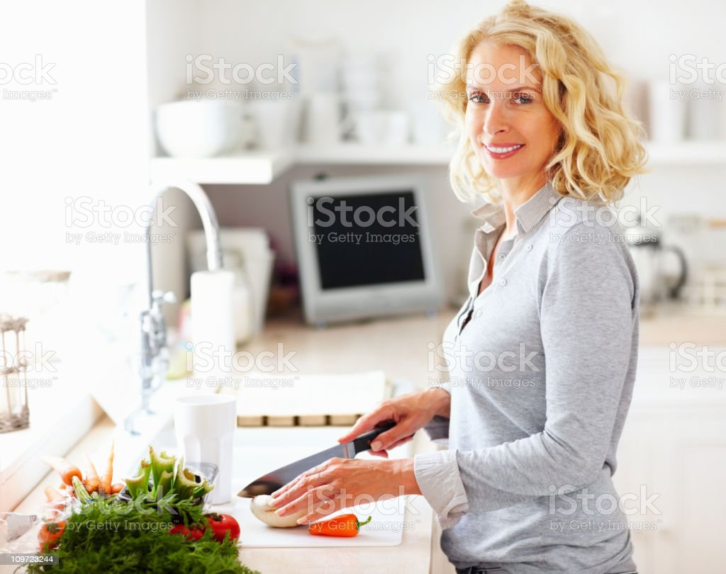 Middle aged woman cutting vegetables in kitchen royalty-free stock photo