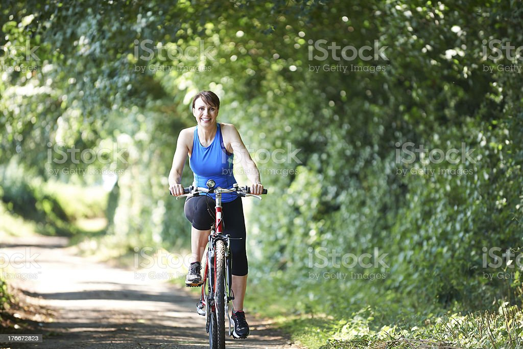 Middle Aged Woman Cycling On Country Road royalty-free stock photo
