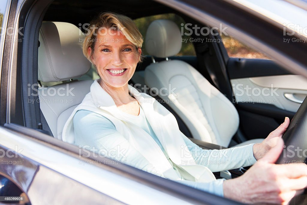 middle aged woman driving a car stock photo