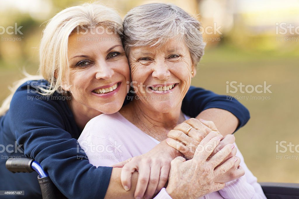 middle aged woman embracing disabled senior mother stock photo