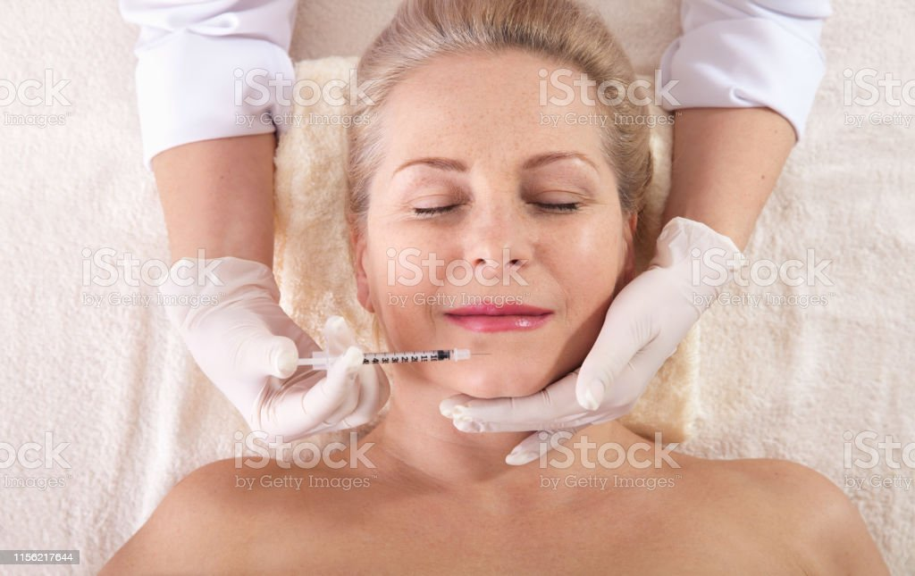 Middle Aged Woman Gets Cosmetic Injection In Her Lips Hyaluronic Acid  Injection For Facial Rejuvenation Procedure Woman In Beauty Salon Plastic