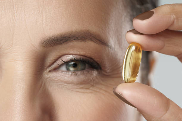 Middle aged woman holding capsule with a fish or krill oil source of Omega-3 fatty acids stock photo