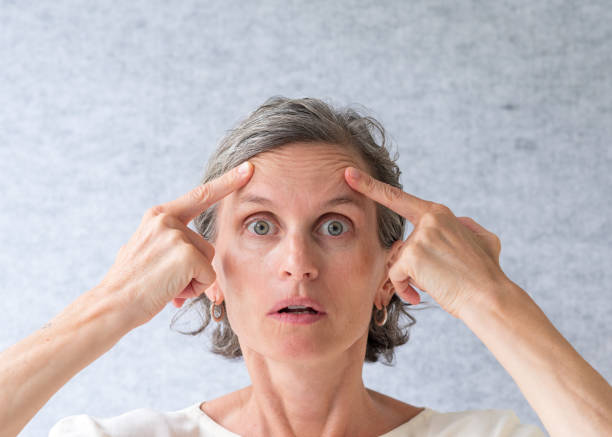 Middle aged woman holding up wrinkles over eyes stock photo