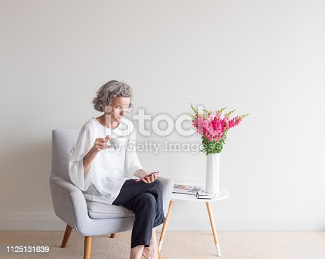 Middle aged woman with grey hair sitting  in retro armchair holding white cup and using smart phone (selective focus)