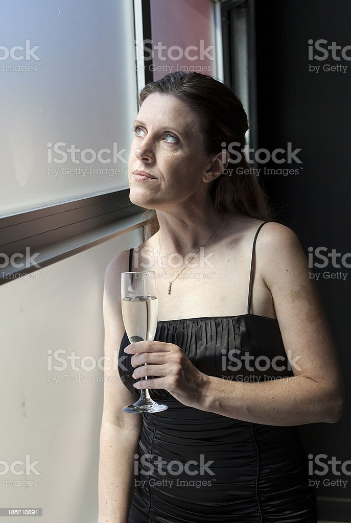 Middle Aged Woman in Black Dress with Champagne royalty-free stock photo
