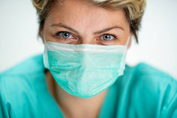 Middle aged woman in healthcare uniform wearing mask stock photo