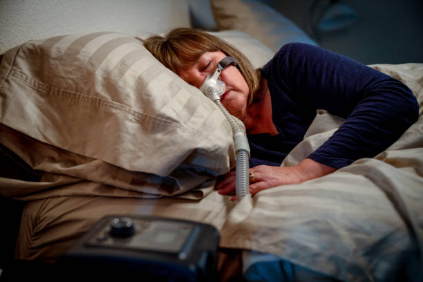 Middle Aged Woman in her Fifties Sleeping Peacefully in Her Bed Using a CPAP Machine to Provide Therapy for Sleep Apnea stock photo