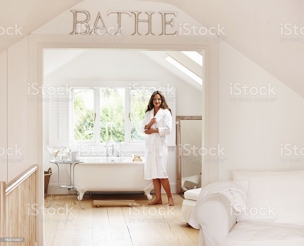 Middle aged woman in robe standing by bathtub at spa stock photo