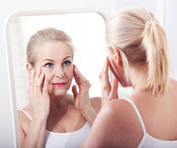 femme regardant les rides en miroir d'âge moyen. chirurgie plastique et injections de collagène. maquillage. visage de macro. mise au point sélective - miroir photos et images de collection