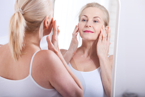 istock Middle aged woman looking at wrinkles in mirror. Plastic surgery and collagen injections. Makeup. Macro face. Selective focus 930768780