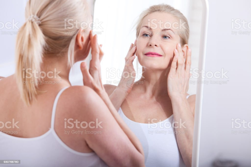 Middle aged woman looking at wrinkles in mirror. Plastic surgery and collagen injections. Makeup. Macro face. Selective focus stock photo