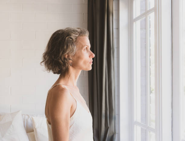 Middle aged woman looking out bedroom window stock photo