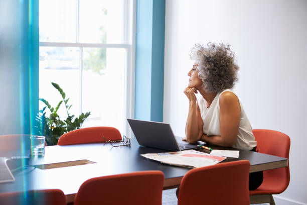 Middle aged woman looking out of the window in the boardroom stock photo