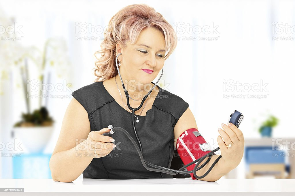 Middle aged woman measuring blood pressure, at home stock photo