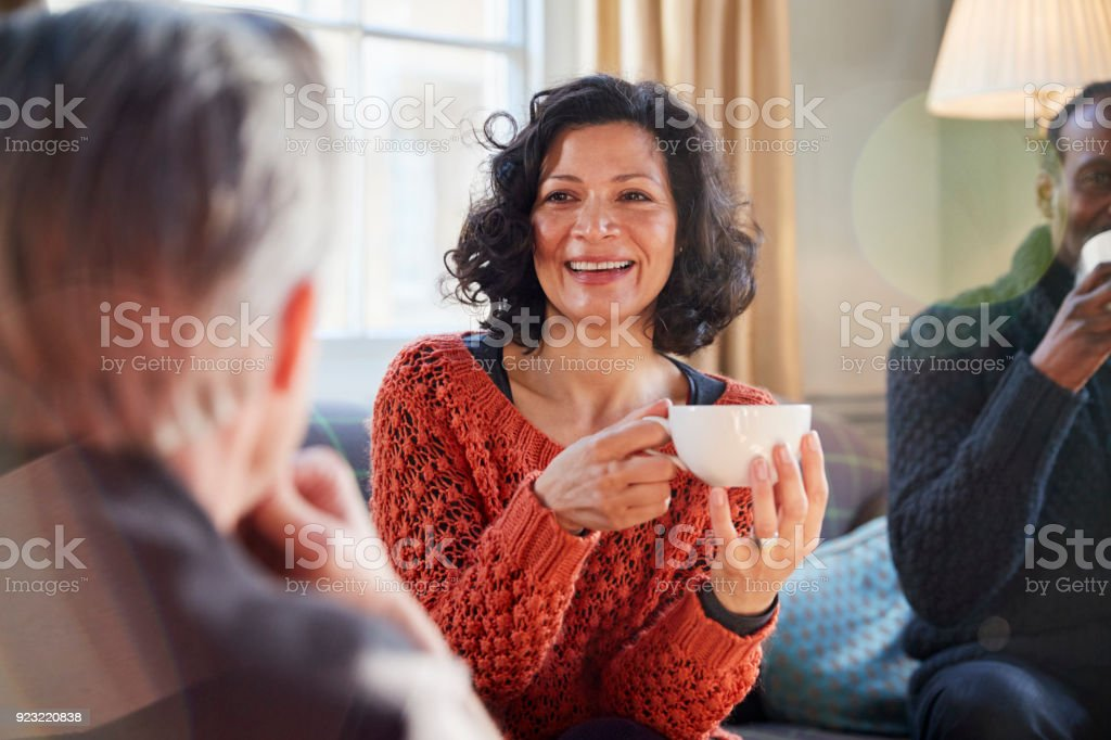 Middle Aged Woman Meeting Friends Around Table In Coffee Shop stock photo