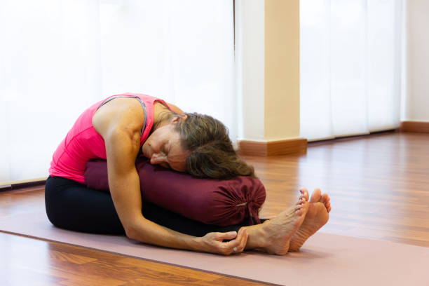 Middle aged woman on pink tank top in paschimottanasana pose resting chest on bolster at bright studio stock photo
