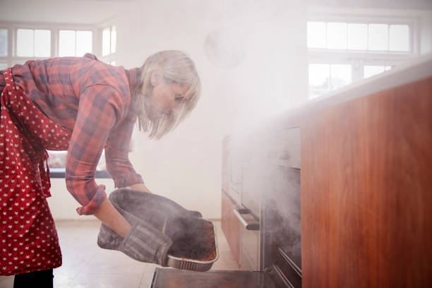 middle aged woman opening smoke filled oven in the kitchen - burned cooking imagens e fotografias de stock