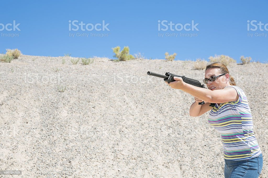Middle aged woman outdoors aming a rifle royalty-free stock photo