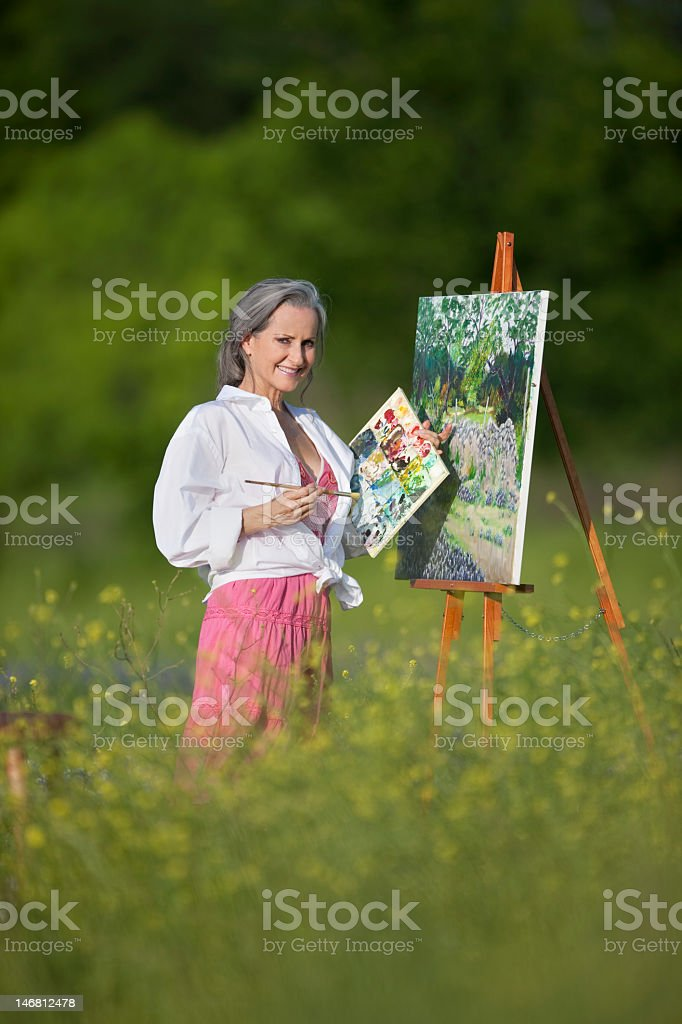 Middle Aged Woman Painting In Field Of Wildflowers royalty-free stock photo