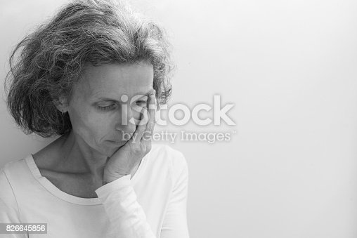 Middle aged woman in white top wiht hand on face against neutral background with copy space to right (black and white, selective focus)