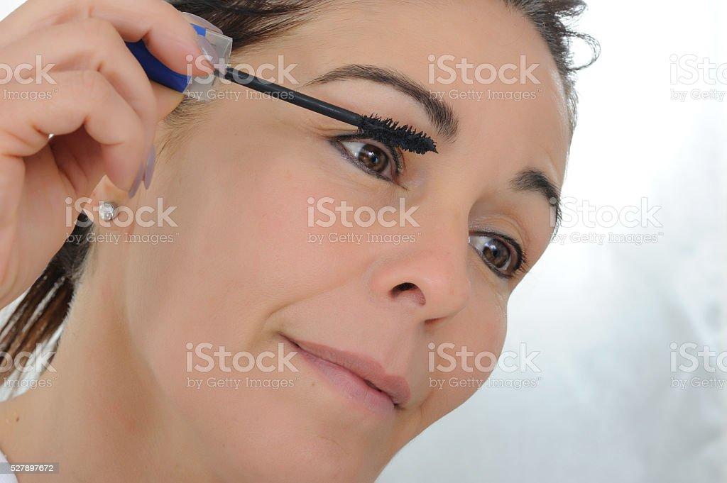 middle aged woman put mascara stock photo