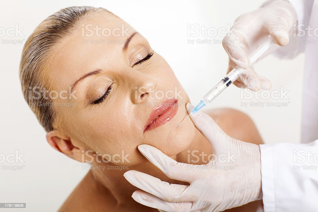 middle aged woman receiving chin injection stock photo