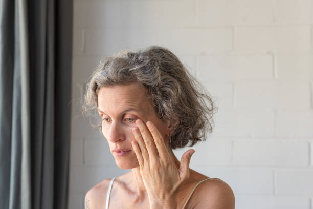 Middle aged woman rubbing eye to wipe tear stock photo