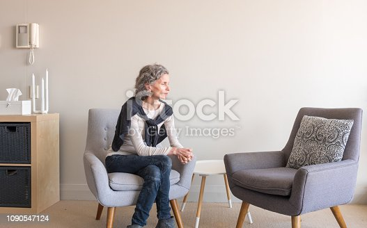 Middle aged woman with grey hair seated alone in living room with empty armchair (selective focus)