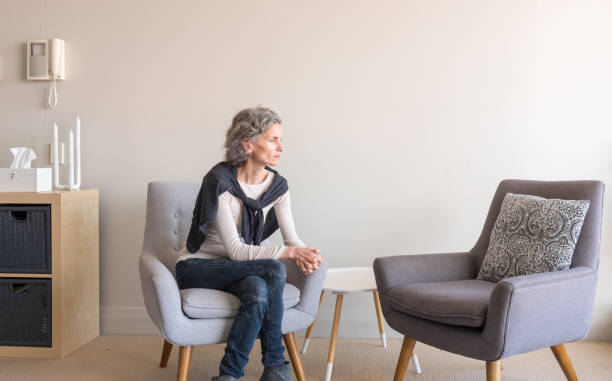Middle aged woman seated alone with empty armchair stock photo