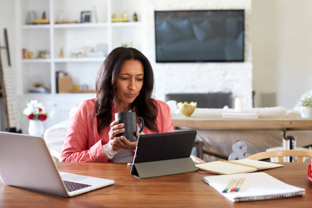 middle aged woman sitting at a table reading using a tablet computer, holding a cup, front view - work from home stock pictures, royalty-free photos & images
