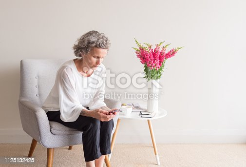 Middle aged woman with grey hair sitting  in retro armchair using smart phone (selective focus)