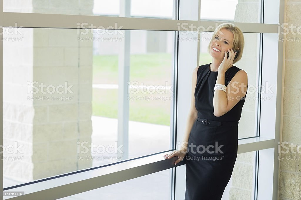 Middle aged woman smiling while talking on her cell phone royalty-free stock photo