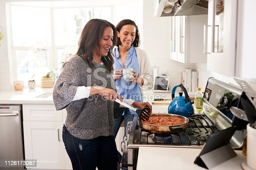 istock Middle aged woman standing in the kitchen cooking at hob following recipe on a tablet computer, her adult daughter standing beside her talking, side view 1126173087