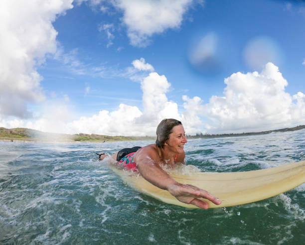 Middle Aged Woman Surfing at the Beach stock photo