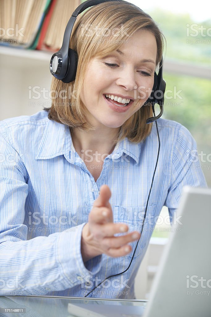 Middle Aged Woman Talking Online Using Headset royalty-free stock photo