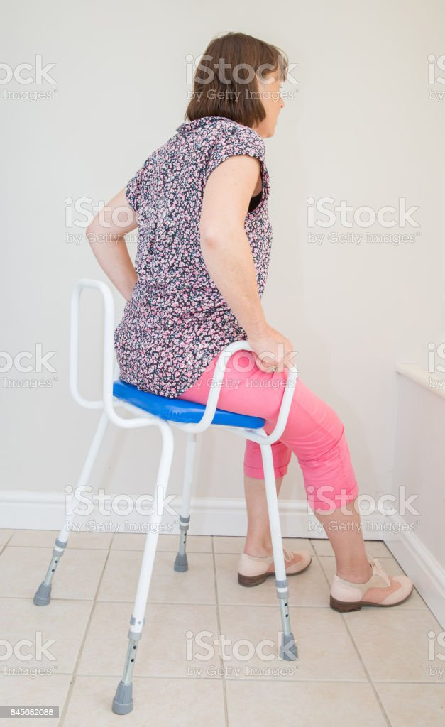 Middle aged woman using a perching stool for easy seating stock photo