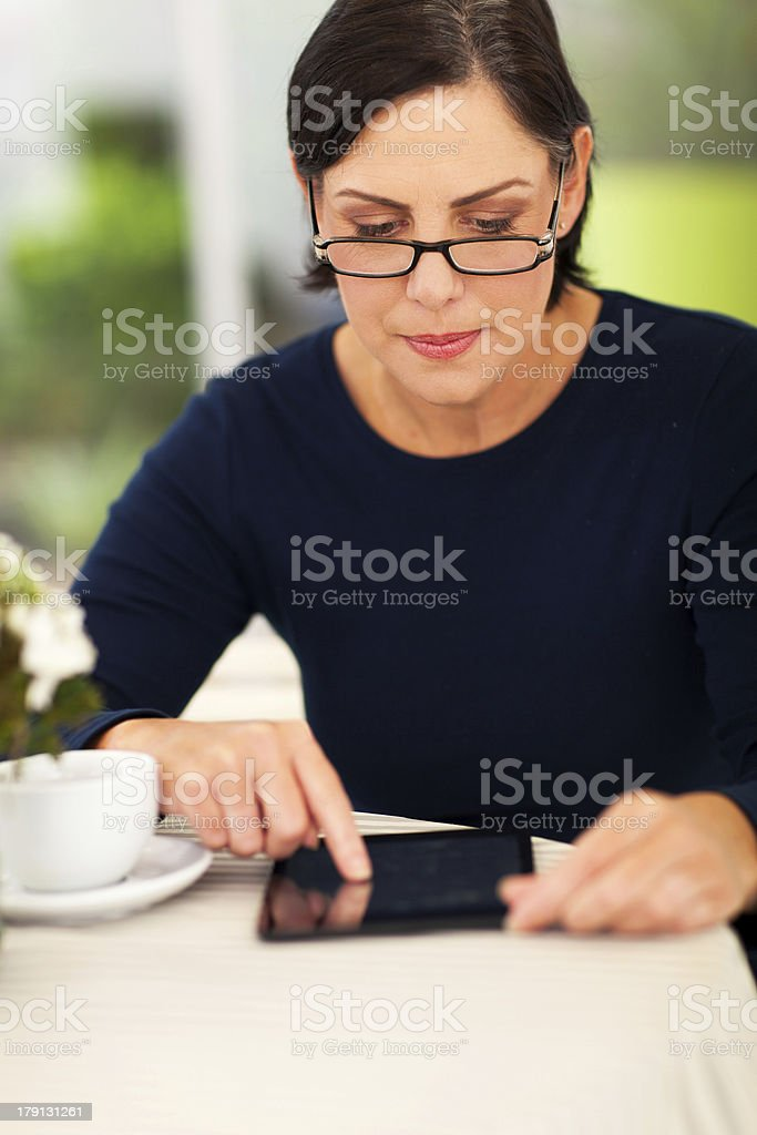 middle aged woman using tablet computer royalty-free stock photo