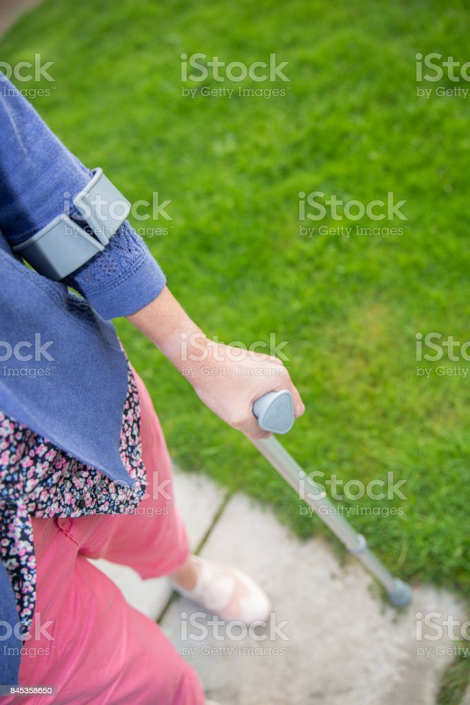 Middle aged woman walking with a single crutch outdoors stock photo
