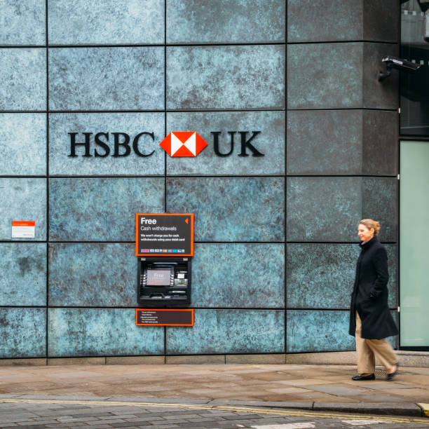 Middle aged woman walks past an Automatic Teller Machine from the HSBC bank advertising free cash withdrawals London, UK- Mar 13, 2018: Middle aged woman walks past an Automatic Teller Machine from the HSBC bank advertising free cash withdrawals hsbc stock pictures, royalty-free photos & images