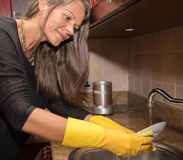 middle aged woman washing dishes. - armband i gummi stock-fotos und bilder