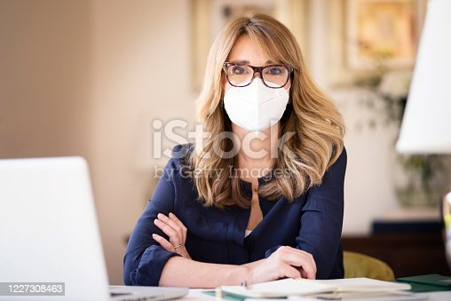 Portrait shot of middle aged woman wearing face mask while working at home on her notebook and text messaging during coronavirus pandemic.