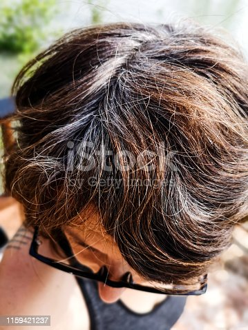One middle aged Woman shows an extreme close-up of her hair follicles.  She is taking a selfie photograph.  Gray hair roots are showing through her brown dyed hair.  A common site during the ageing process.