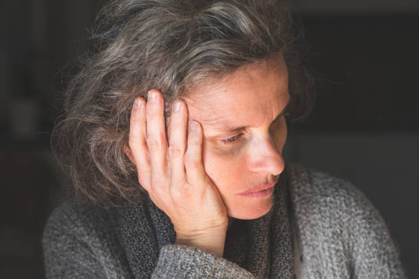 Middle aged woman with grey hair sitting in the dark stock photo