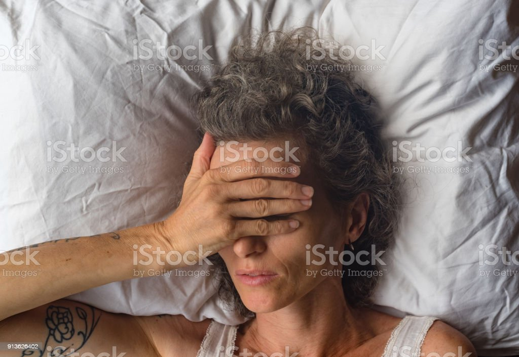 High angle close up view of middle aged woman sleeping on pillow with...
