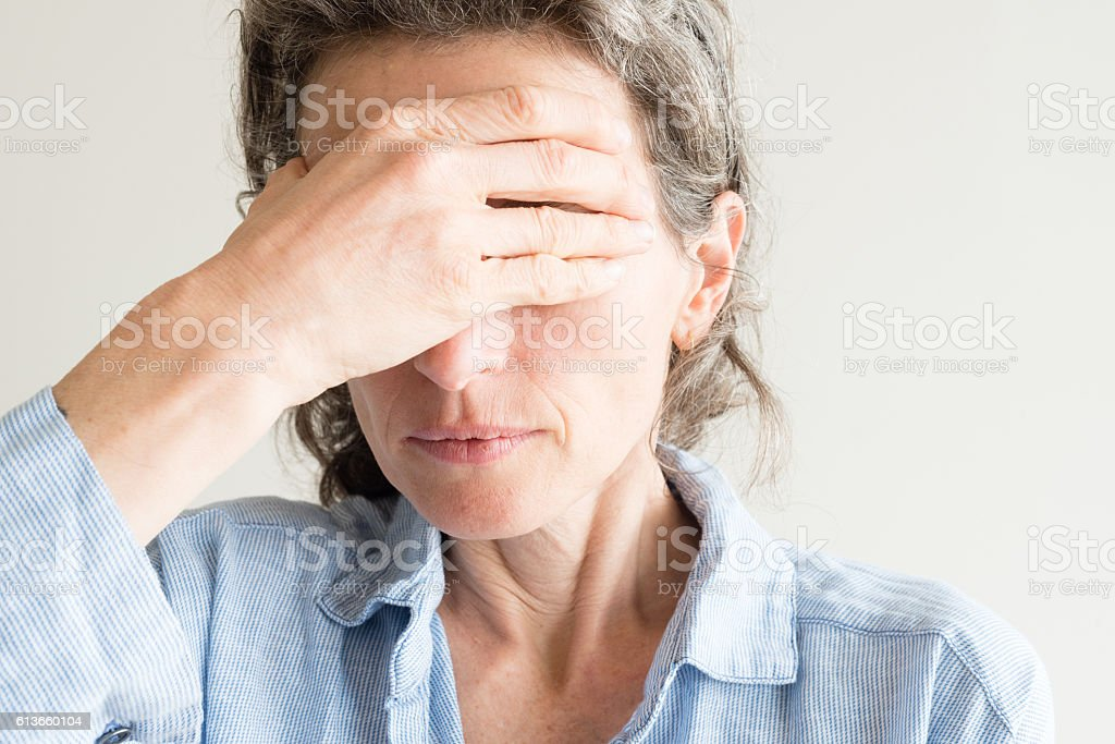 Middle aged woman with hand over eyes - Royalty-free Adult Stock Photo